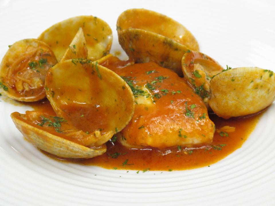 Lomos de merluza con almejas al Txakoli y tomate